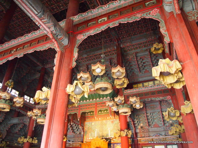 The ceiling of Changdeokgung Palace, with red pillars, ornate carvings around the lights and in the ceiling, in turquoise, red and green.