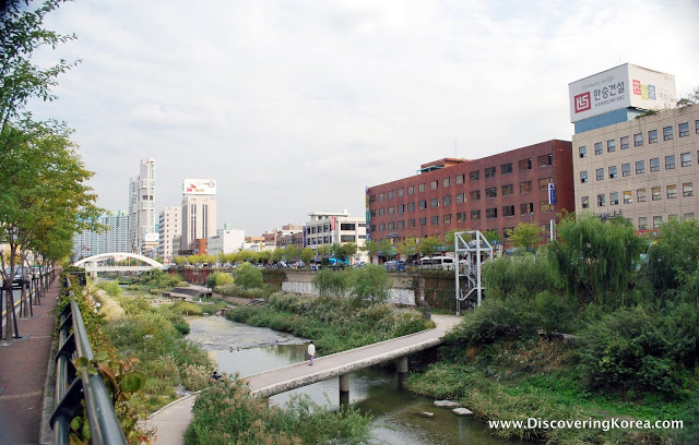 In the center of the frame is a bridge over Cheonggyecheon stream, with a backdrop of brick and stone buildings, and vegetation.