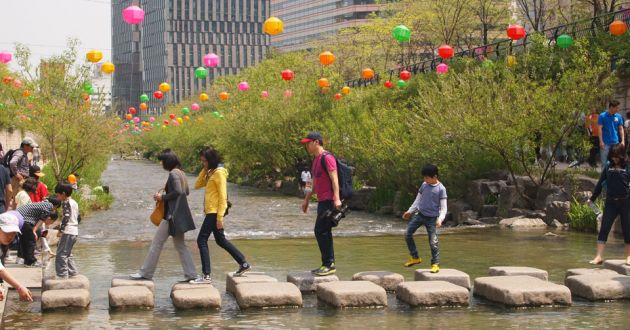 Paving stones crossing the Cheonggyecheon stream with people walking and multicolored paper lanterns in the background.