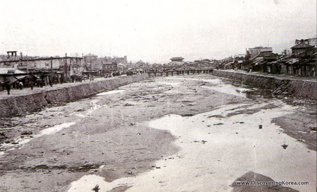 Historical image of Cheonggyecheon, an empty wasteland area with dilapidated houses each side, and almost dry riverbed to the center of the frame.