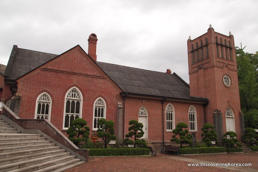 The red brick building of Chungdong church in Seoul. Arched windows with white frames, and a bell tower to the right of the frame. Ornamental bushes in the foreground.