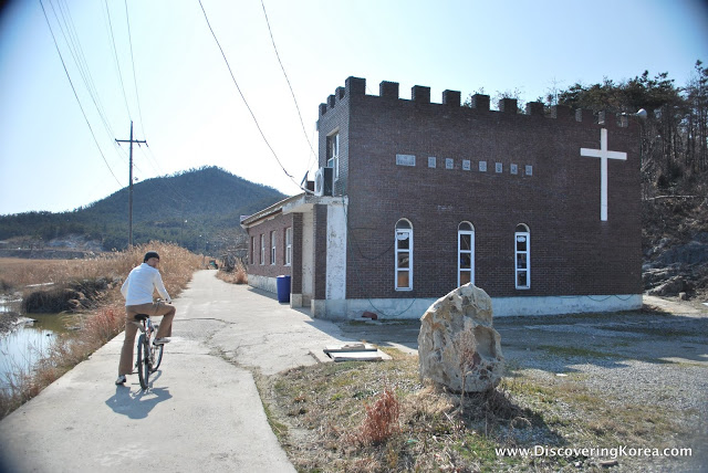 On the right of the frame is a brick building, a church, with a white cross on the outside and small arched windows, to the left is a cyclist, pausing to look back at the camera.