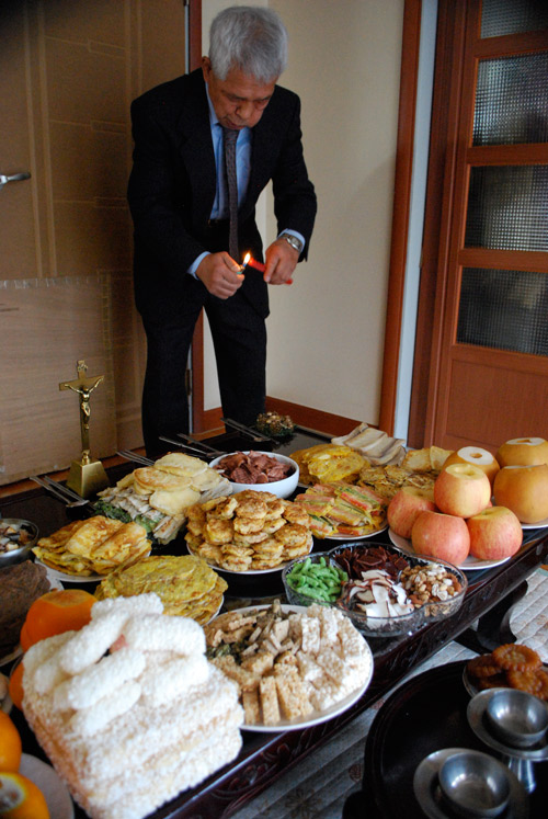 A man lights a candle over a table full of food for Chuseok. Plates of various Korean specialties on a black surface.
