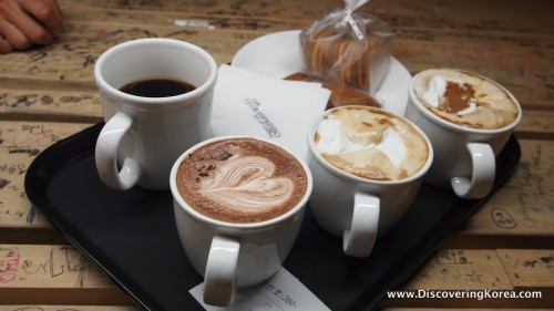 Four cups of coffee on a black tray, on a wooden table with a white plate and a packet of cookies.