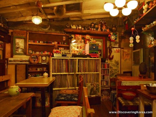 A dimly lit room at Coffee Han cafe in Seoul, with wooden tables and chairs, a bookcase of old LP records, and various curios and ornaments on wooden shelves.