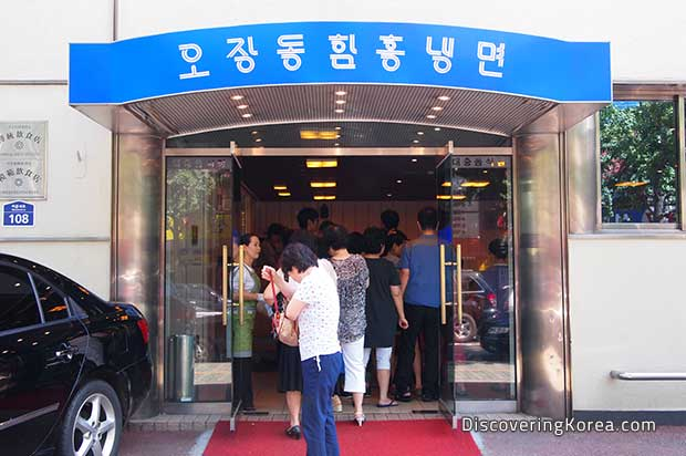 Entrance to a noodle shop in Seoul. Glass doors with a blue sign above, a large group of people in a line waiting to go in. To the left of the frame is a black car.