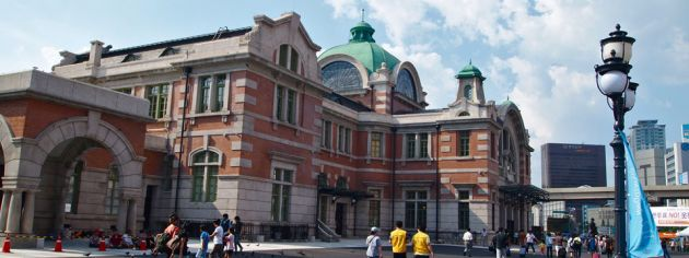 Exterior of the Culture Station, Seoul, a colonial brick and stone building with a green dome, pedestrians outside and a lamp post to the right of the frame, seen on a sunny day with a few wispy clouds.