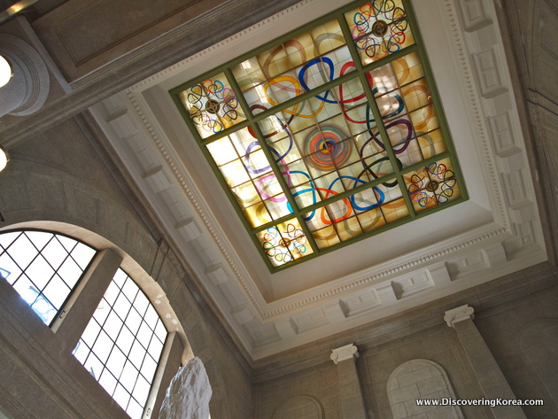 Ornate multicolored ceiling detail in the Seoul Culture Station. White inlays and stained glass. To the left of the frame, the domed side window can be seen, set into the light stone walls.