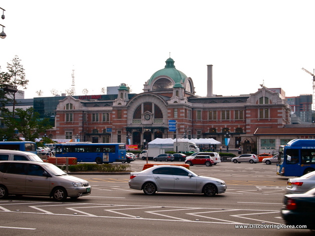Outside view towards Seoul's Culture Station, a brick and stone colonial building, with a green central dome. In the foreground is a car park with several cars, and buses.