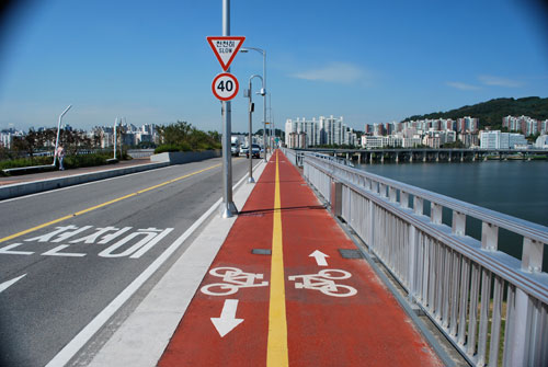 Looking over the bridge towards the city, the river on the right of the frame, a cycle lane in the center of the frame and road on the left.