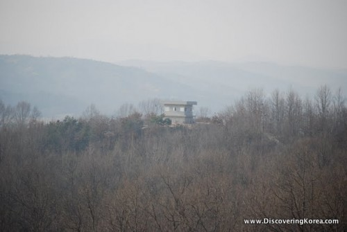 A solitary house sits in scrubby bushland with mountains in the background. DMZ nature preserve.