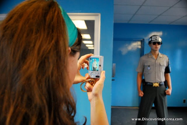 To the right of the frame a woman takes a photo on a digital camera of a solider inside the DMZ. He stands upright with fists clenched, against a bright blue background.