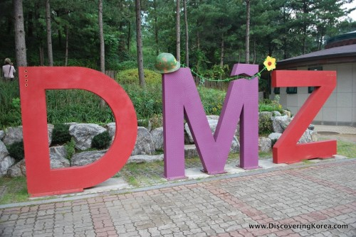 The letters DMZ in red and purple in front of trees.