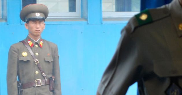 A Korean soldier stands against a blue wall, with a soft focus close up of another soldier's shoulder in the foreground.