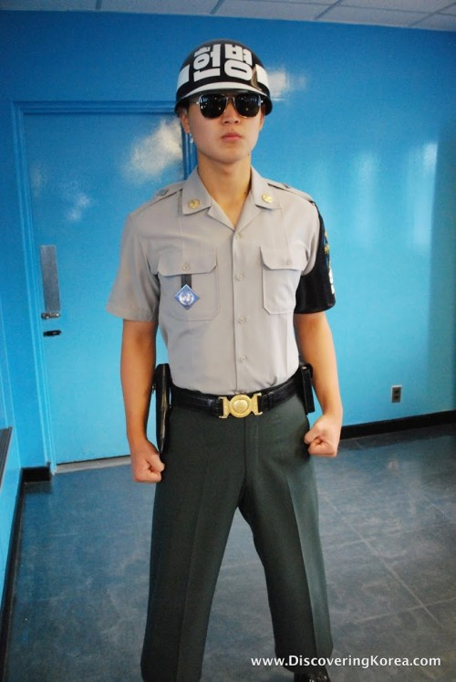 A soldier in the DMZ stands with his fists clenched in front of a blue wall.