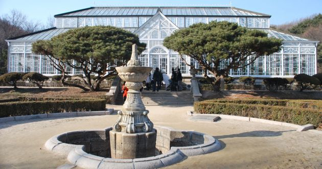 Exterior view of Daeonsil, a large glass house with white framework, an A frame entrance. In front is a courtyard with a stone fountain leading up to the steps, two large trees flanking the entrance.
