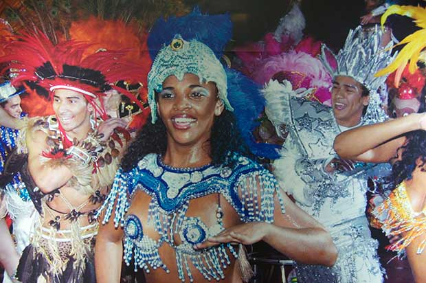 Dancers at Lotte World, a woman dressed in a blue glittery outfit and headdress at the center of the frame, surrounded by men dressed in various fancy dress themes.