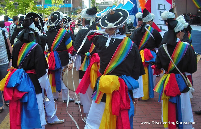 Dancers dressed in black and white robes, with black and white hats and a rainbow sash parade down the street in Seoul.