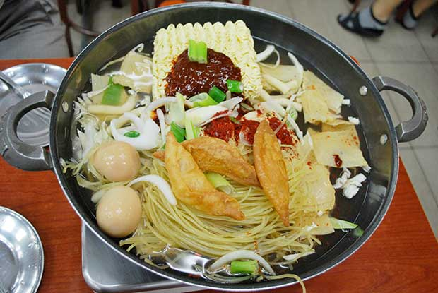 A metal pan, containing two types of noodles, a broth, some vegetables and meat, ready for cooking on a table top stove.