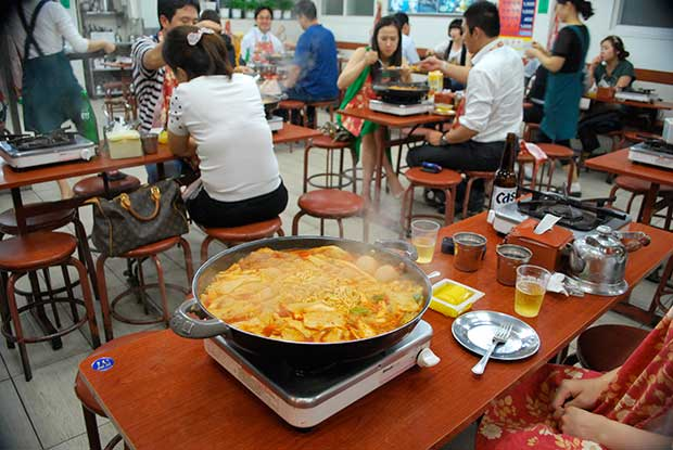 A crowded restaurant, in the background, people sitting on wooden stools eating, in the foreground a metal pan on a table top stove, simmering with noodles, meat, vegetables and sauce, the traditional ddeokbokki.
