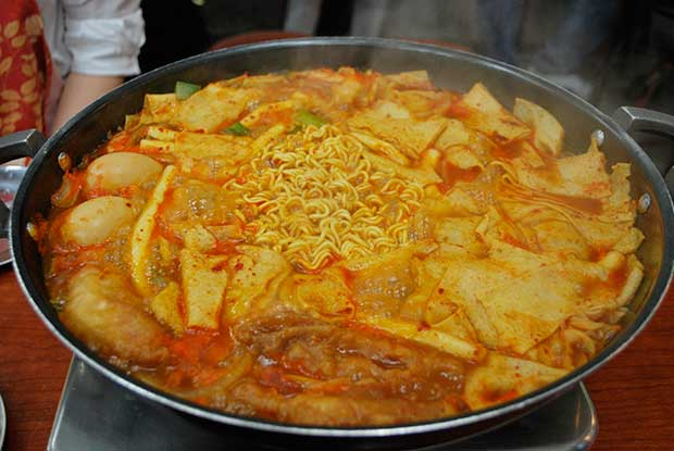 A close up of a metal pan with simmering ddeokbokki, a traditional Korean dish of noodles, vegetables, sauces and meat.