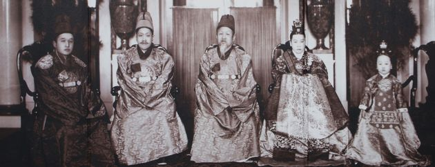 A sepia image of the Korean royal family with Emperor Gojong in the center. Five people sitting in a row, traditionally dressed in long gowns.