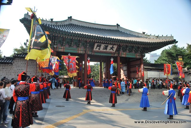 Changing of the guard at Deoksugung gate. Traditionally dressed in black, red, and blue capes, the guards, carrying flags are outside the ornate gate with observers in the background.