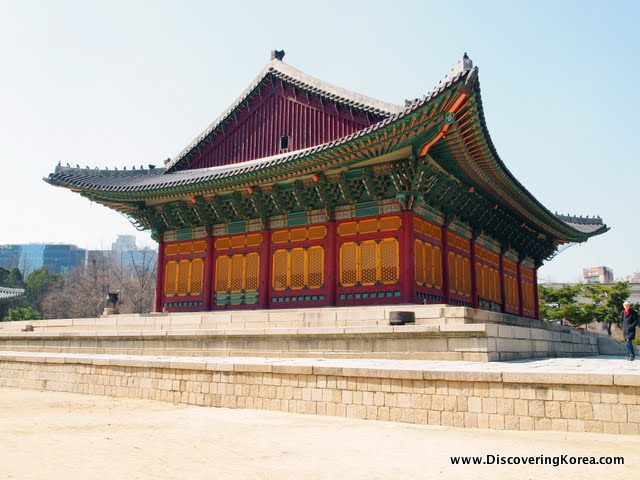 Exterior view of Jeonghwangeon throne hall. An ornate building in red, orange and green stands on a stone platform. In place of windows is orange fretwork, and ornate carving in the eaves.