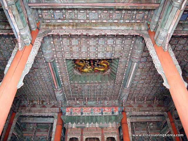 Ceiling detail in the Jeonghwangeon throne hall. Two orange pillars flank the multicolored, symmetrical detail of the ceiling, with a central gold motif, of dragons.