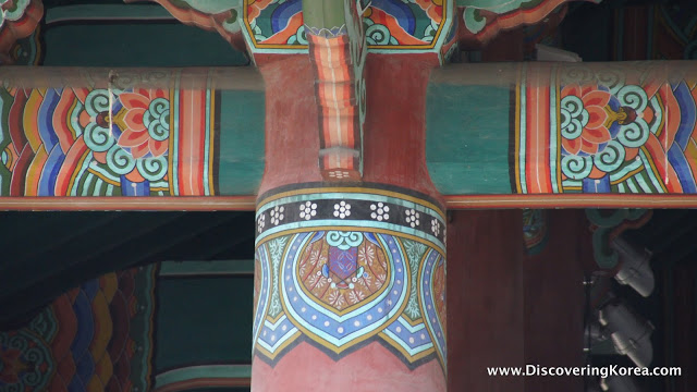 Close up of the intricate paintings on the Bosingak belfry, on red wood, multicolored designs of lotus leaves and other traditional patterns.