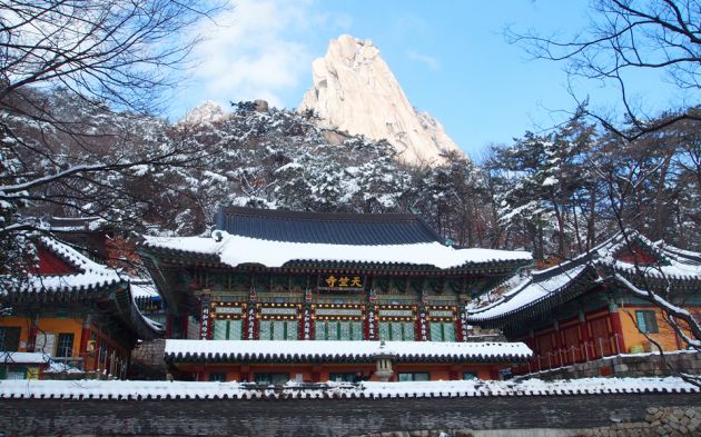 Dobongsan mountain covered in snow in the background and an ornate building in front.