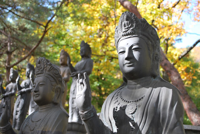 Religious figures made of stone with soft focus trees in the background.