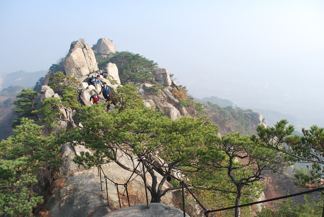 Rocky outcrop trail up Dobongsan mountain, with trees in the foreground and soft focus landscape behind.