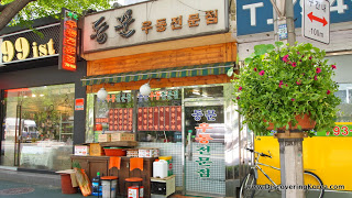 Shop front of a restaurant in Yongsang, with tables outside, and an ornamental bush to the right of the frame.