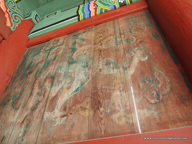 Detail showing faded artwork at Dongmyo shrine, on wood, with red surrounds and green detailing above.