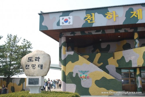 Outside of the Dora Observatory, painted in camouflage, with a sign on the left painted on a rock. Pedestrians milling in the background.