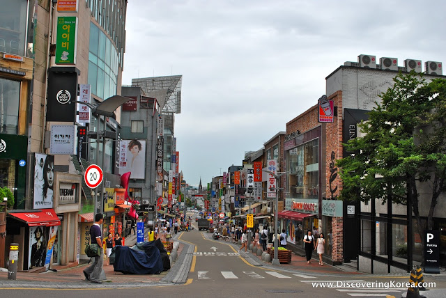 View down a street in Edae, Seoul, showing pedestrians and shops on both sides, with multicolored signs, on a cloudy day.