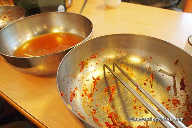 Two metal bowls on a wooden surface, to the right of the frame the bowl is empty, but for some remnants of red sauce, with chopsticks. To the left of the frame, the metal bowl has a cloudy broth.