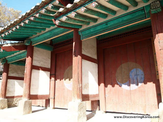 Wooden entrance gatehouse to Suwon, red doors with yin and yang sign on them, yellow log roof, in the sunshine.