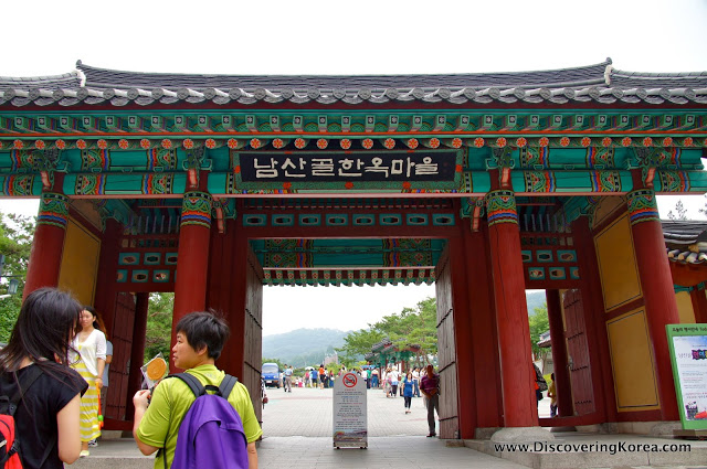 The ornate entrance to Namsangol hanok village, with red pillars, turquoise and yellow detail. The view through the gateway is towards a soft focus mountain, and in the foreground are pedestrians walking.