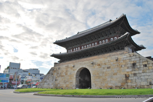 External view of the entrance to Suwon Hwaseong fortress showing an arched doorway in a stone wall and ornate roof.
