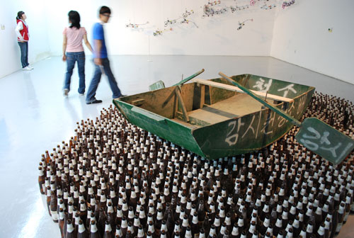 Exhibit at Gwangju biennale, a green wooden boat with oars, and white Korean lettering, sits atop a large number of bottles, arranged to look like the sea. In the background are people walking against a soft focus white wall.