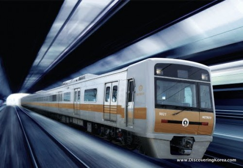 Close up of a metro train, white with a yellow stripe, speeding through a metro tunnel in Seoul.