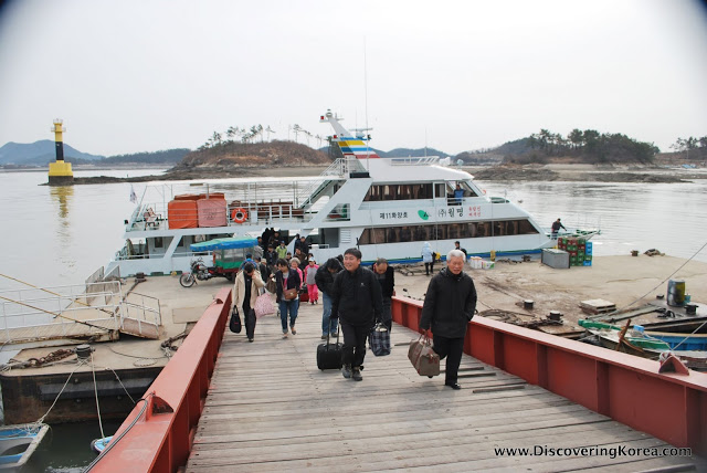 The ferry moored at Seonyudo with passengers disembarking and walking up a sloping walkway. In the background is the harbor.