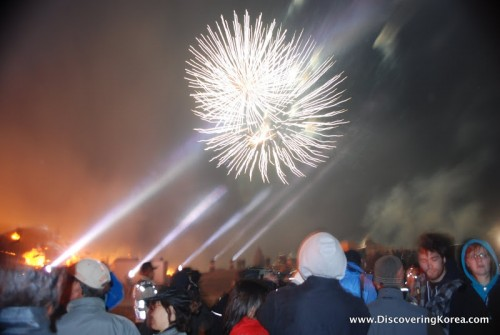 A fireworks display on a soft focus background, with a crowd of people watching, on Jeju island.
