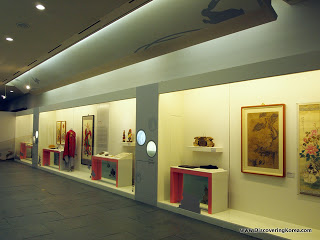 Large glass cabinets in the Folk museum of Korea, containing pictures, figurines and sculpture exhibits.