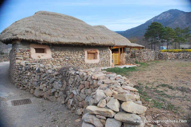 A small stone house, with a path and stone wall leading up to it. The cottage has a thatched roof and small mullion windows. In the background is a mountain and trees.