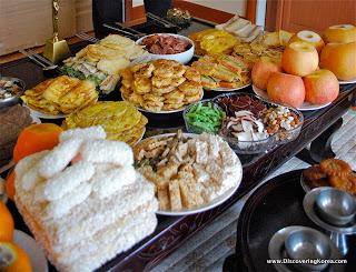 A table laden with a feast for Seollal, there are pancakes, sweet treats, apples, and noodle dishes.