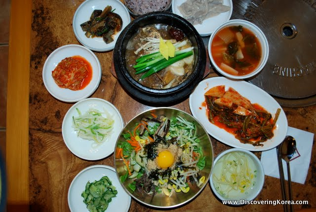 A feast, a wooden table, with many condiments on small white plates, in the center is a dark bowl with meat stew and vegetables, and a metal bowl with a noodle dish with an egg on top.
