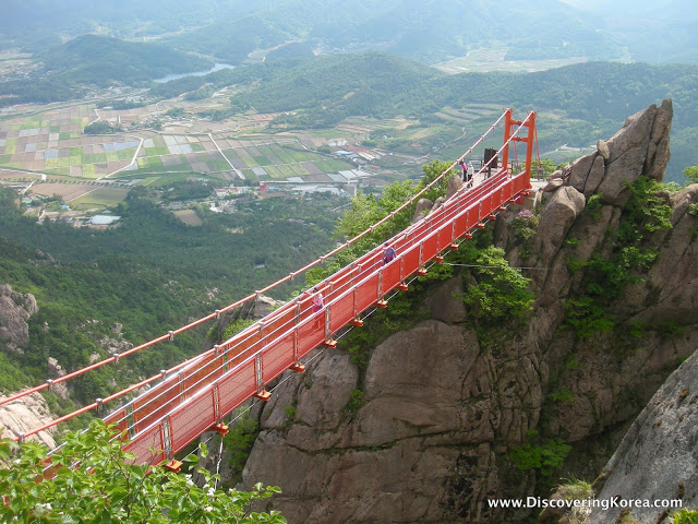 Aerial view of a red footbridge connecting two rocky peaks in Wolchulsan National Park, in the background, far below, is farmland in soft focus.